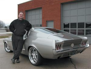 Troy Trepanier stands next to the FastForward Fastback 1967 Mustang